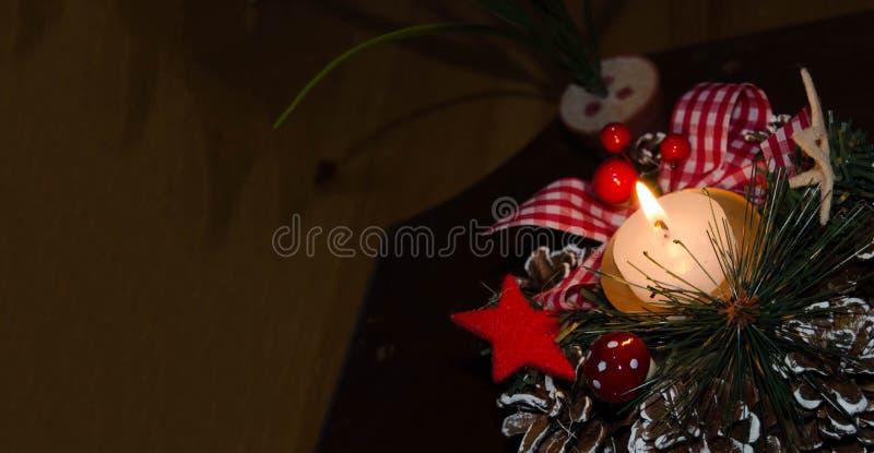Vela y decoración ardiendo de la Navidad sobre nieve y fondo de madera, tiro elegante con humor festivo imágenes de archivo libres de regalías
