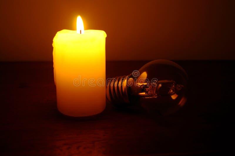 Vela y lámpara ardientes en la mesa foto de archivo
