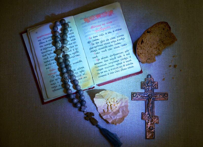 Velada de oración eslava libro de oración y del texto abiertos de la iglesia, crucifijo y otros símbolos de la fe cristiana ortod fotografía de archivo libre de regalías