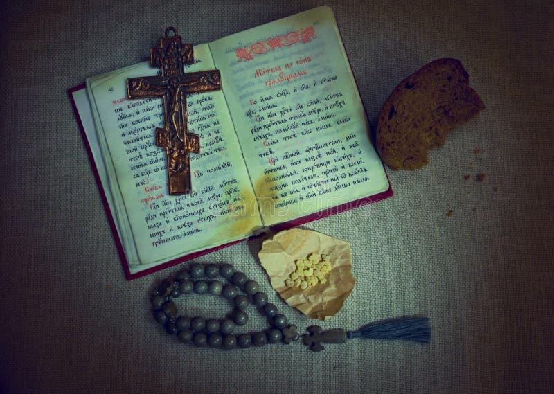 Velada de oración eslava libro de oración y del texto abiertos de la iglesia, crucifijo y otros símbolos de la fe cristiana ortod fotos de archivo