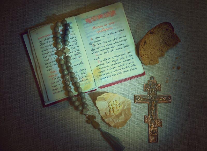 Velada de oración eslava libro de oración y del texto abiertos de la iglesia, crucifijo y otros símbolos de la fe cristiana ortod fotografía de archivo