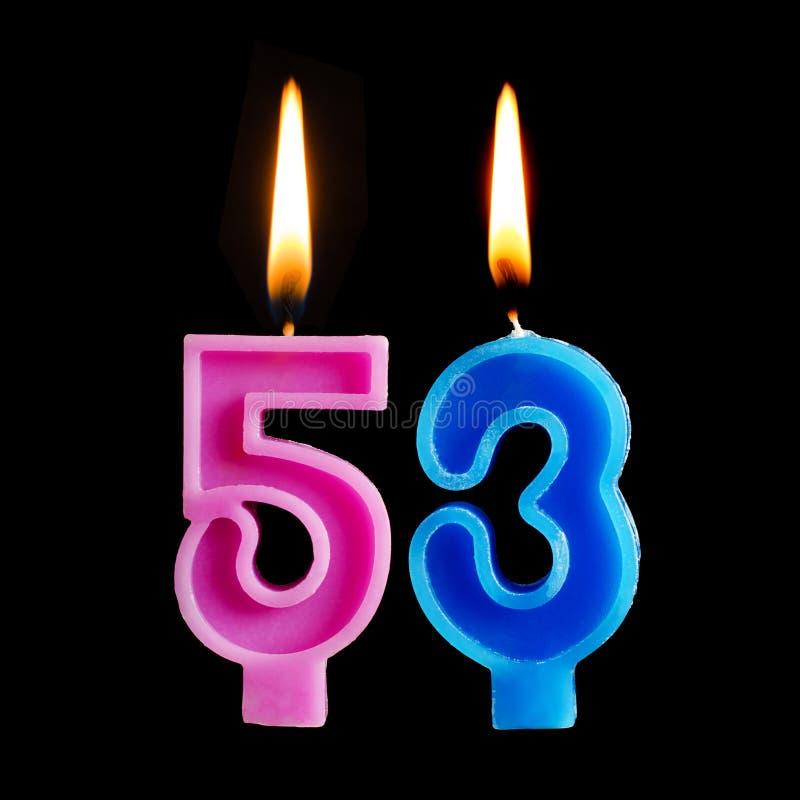Velas ardentes do aniversário sob a forma de 53 cinquenta e três para o bolo isolado no fundo preto foto de stock royalty free