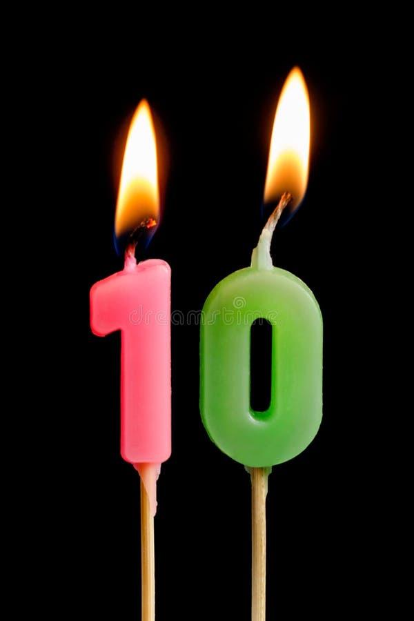 Velas ardentes sob a forma de dez figuras números, datas para o bolo no fundo preto O conceito de comemorar um bi fotografia de stock