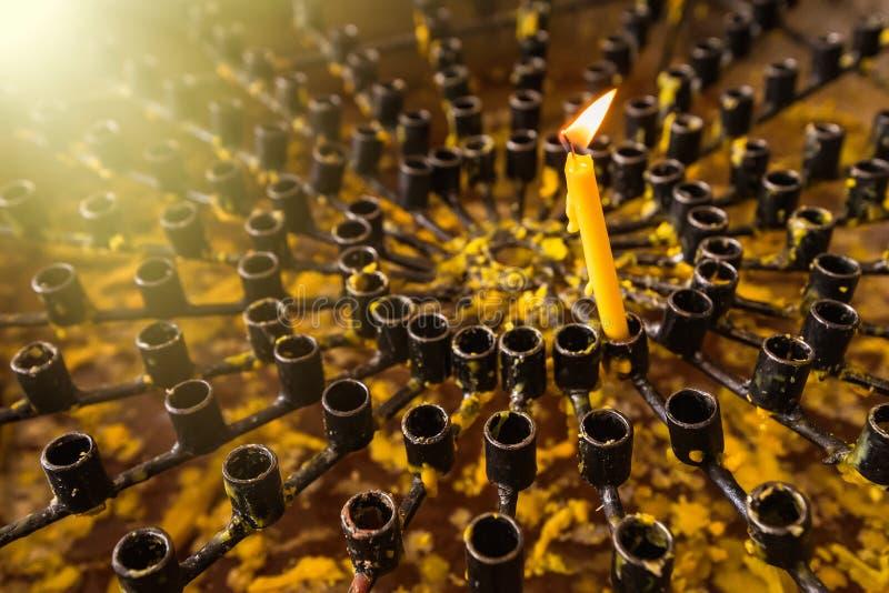 Velas ardiendo de la cera en un primer del templo budista Rituales de la adoración de deidades y de dioses en Asia Meditación y a imagen de archivo libre de regalías