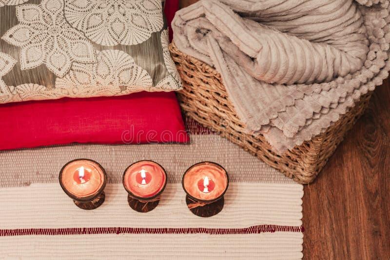 Velas ardiendo del aroma del balneario en la cáscara del coco, las almohadas y la tela escocesa, fondo interior casero acogedor imagenes de archivo