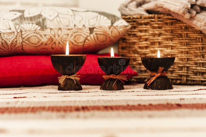 Velas ardiendo del aroma del balneario en la cáscara del coco, las almohadas y la tela escocesa, fondo interior casero acogedor fotografía de archivo