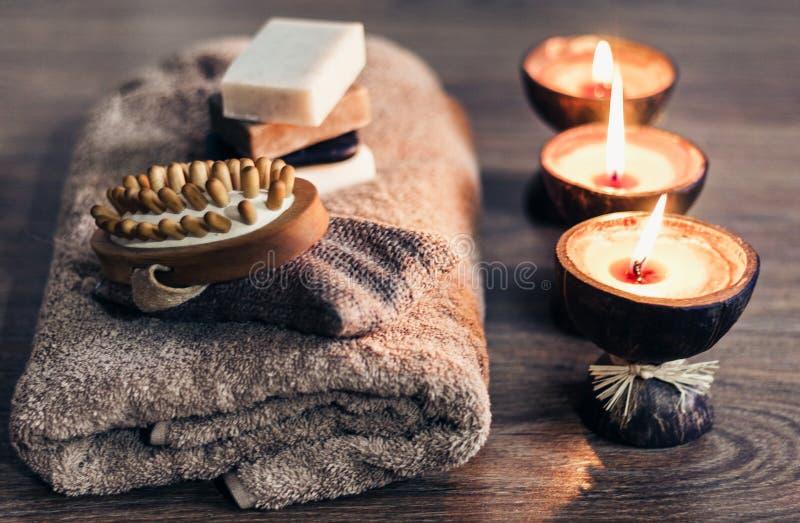 Velas ardiendo del aroma del balneario en la c?scara del coco, el jab?n hecho a mano, la toalla y el toallita, fondo del concepto imagenes de archivo