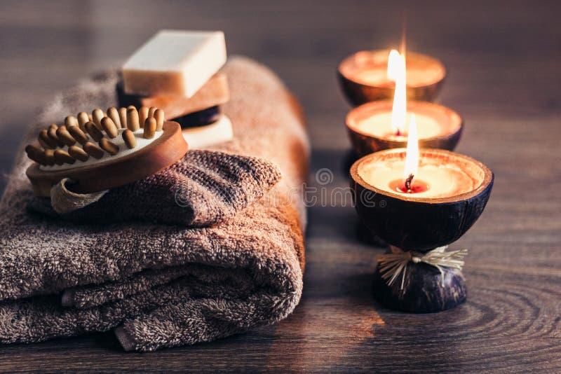 Velas ardiendo del aroma del balneario en la c?scara del coco, el jab?n hecho a mano, la toalla y el toallita, fondo del concepto foto de archivo