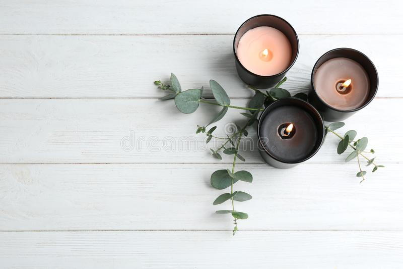 Velas ardiendo y ramas verdes en la tabla de madera blanca, endecha plana fotos de archivo