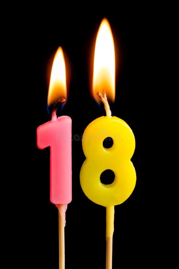 Velas ardientes bajo la forma de 18 dieciocho figuras números, fechas para la torta aislada en fondo negro El concepto de celebra fotos de archivo