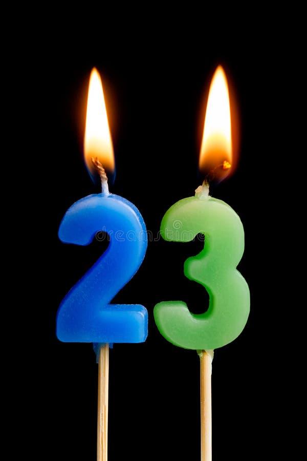 Velas ardientes bajo la forma de 23 veintitrés números, fechas para la torta aislada en fondo negro El concepto de celebración imagenes de archivo