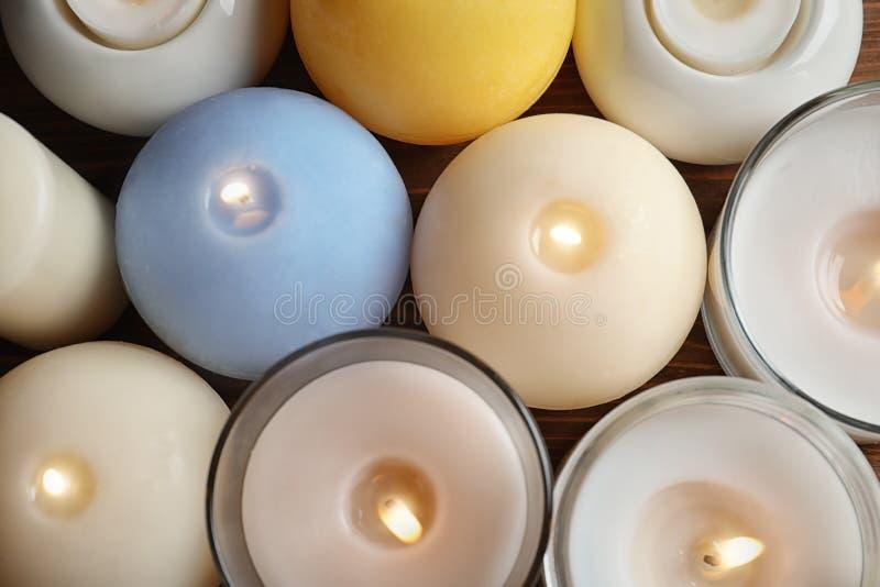 Velas ardientes de la cera de diversos formas y colores imágenes de archivo libres de regalías