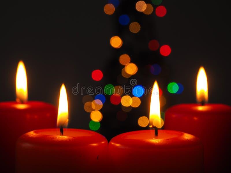Velas ardientes del advenimiento con las luces del árbol de navidad imágenes de archivo libres de regalías