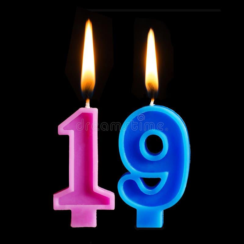 Velas ardientes del cumpleaños bajo la forma de 19 diecinueve figuras para la torta aislada en fondo negro imagenes de archivo