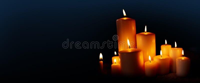 Velas ardientes en la noche oscura imagenes de archivo