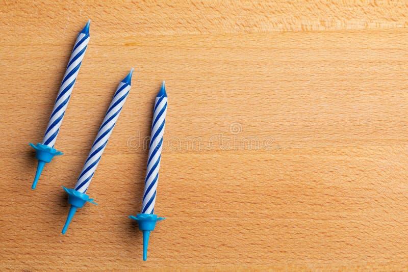 3 velas azules del cumpleaños en fondo de madera Para la tarjeta de felicitación del cumpleaños Espacio para insertar el texto imagenes de archivo