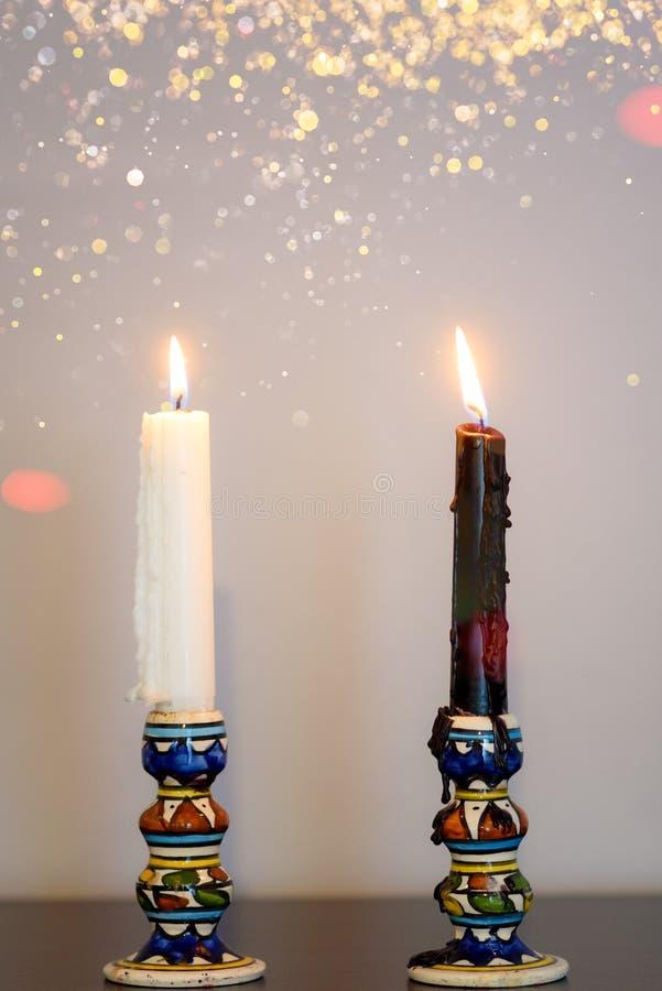 Velas blancas y negras Dos velas ardientes en la tabla de madera contra la pared gris foto de archivo libre de regalías