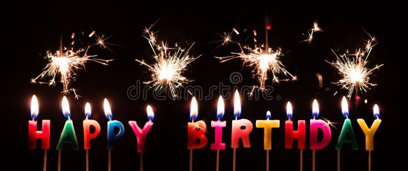 Velas coloridas del feliz cumpleaños con los fuegos artificiales de la bengala, en fondo negro fotografía de archivo libre de regalías