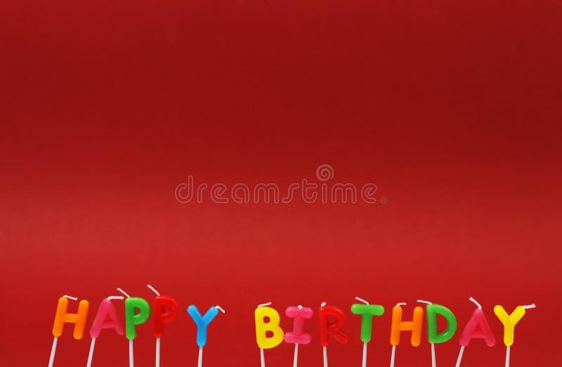 Velas coloridas do feliz aniversario no fundo vermelho fotografia de stock royalty free