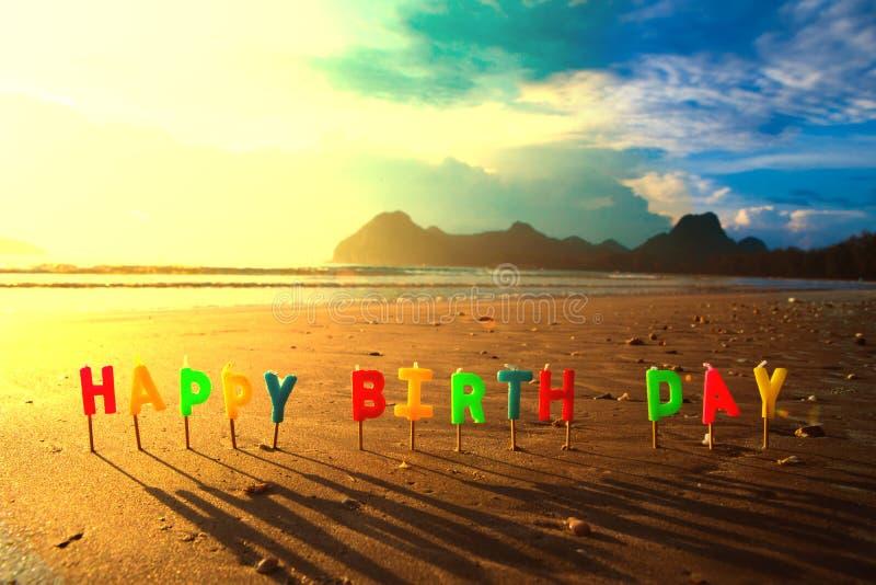 Velas coloridas do feliz aniversario no nascer do sol da praia foto de stock royalty free