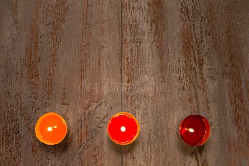 Velas coloridas en los tableros de madera imagen de archivo libre de regalías