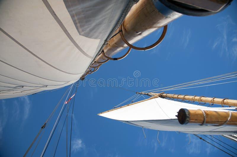 Velas completas em mastros de madeira de Saliboat com céu azul imagens de stock royalty free