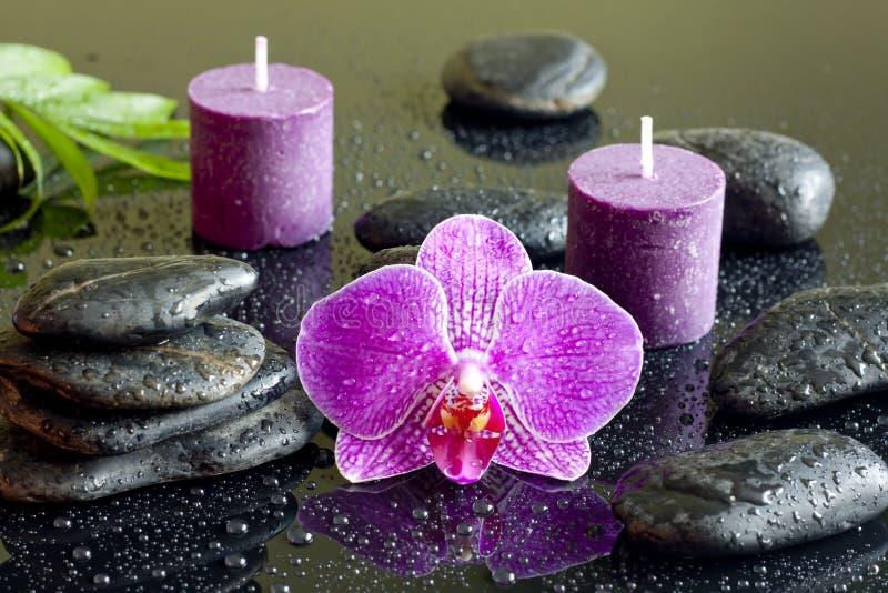 Velas da orquídea e conceito roxos dos termas das pedras do zen fotos de stock