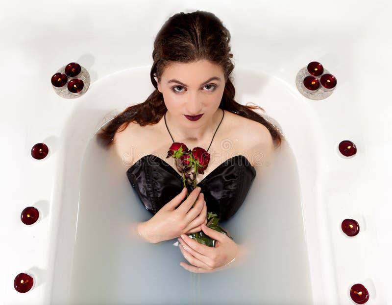 Velas das rosas vermelhas do banho maria do leite da menina fotografia de stock