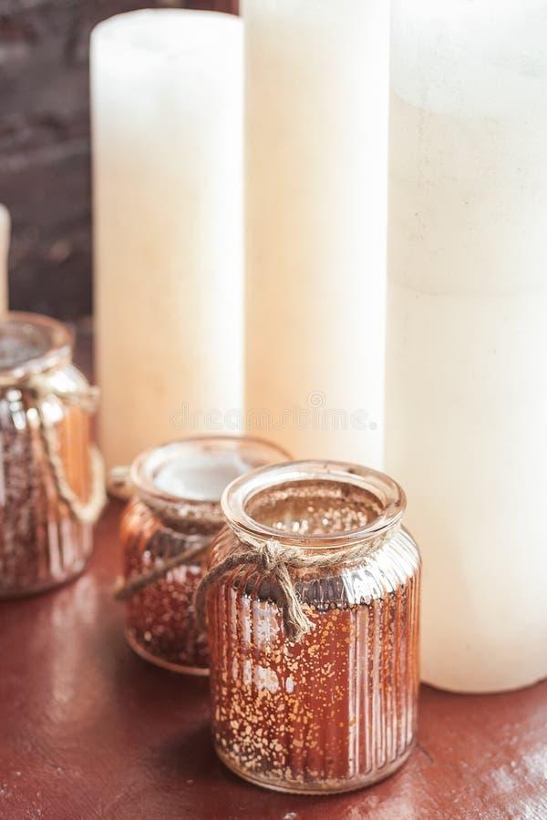 Velas de la Navidad blanca y un tarro de cristal con el travesaño derecho del onwindow de la guita rústica fotos de archivo libres de regalías