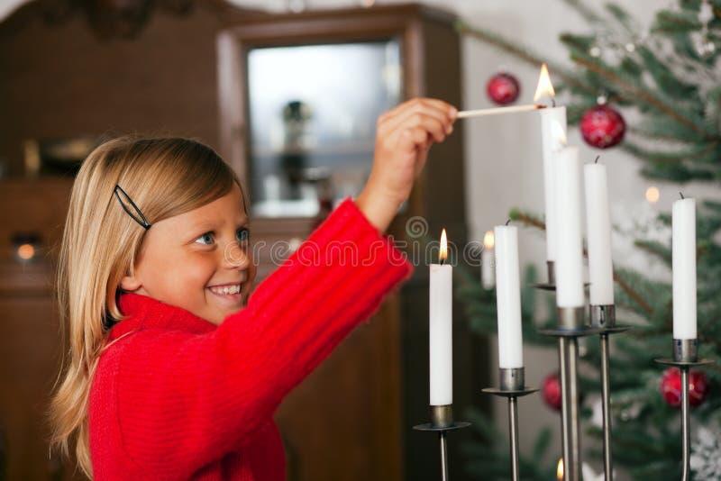 Velas de la Navidad de la iluminación del niño fotos de archivo