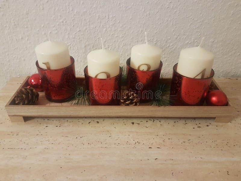Velas de la Navidad y potes hermosos de rojo para adornar la tabla imagen de archivo