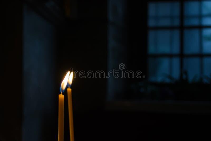 Velas de queimadura da cera contra a janela em uma sala escura fotografia de stock