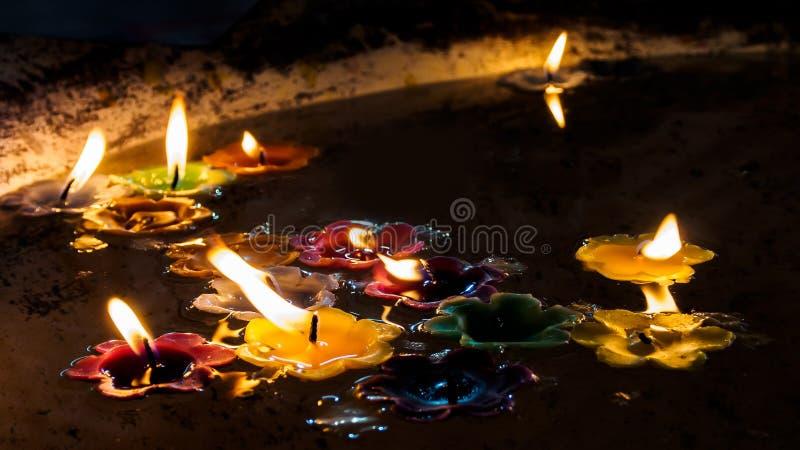 Velas de queimadura da flor na água na noite foto de stock royalty free
