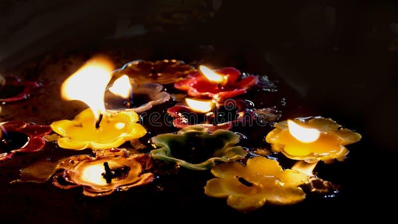 Velas de queimadura da flor na água na noite imagem de stock