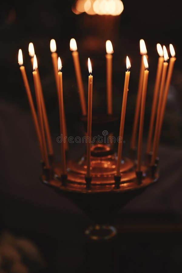 Velas de queimadura no castiçal de bronze contra o fundo escuro em casa Velas no interior Estilo do vintage fotografia de stock