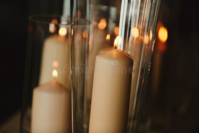 Velas de queimadura no castiçal de bronze contra o fundo escuro em casa Velas no interior Estilo do vintage fotografia de stock royalty free