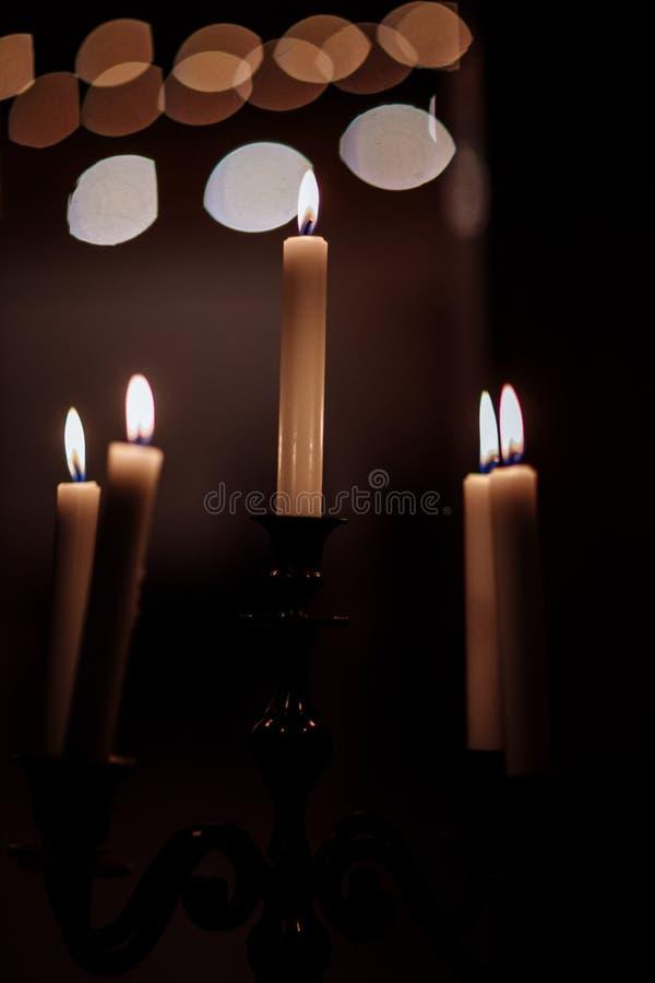 Velas de queimadura no castiçal de bronze contra o fundo escuro em casa Velas no interior Estilo do vintage foto de stock