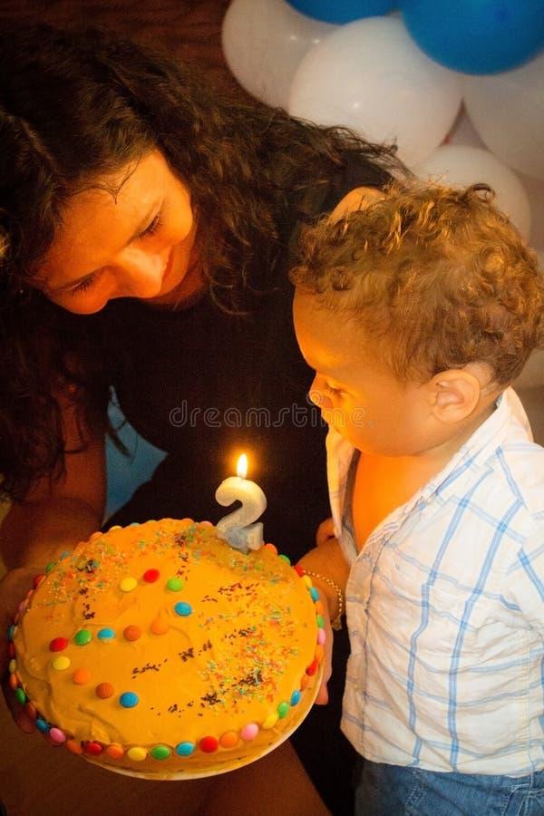 Velas de sopro da criança no bolo de aniversário imagens de stock