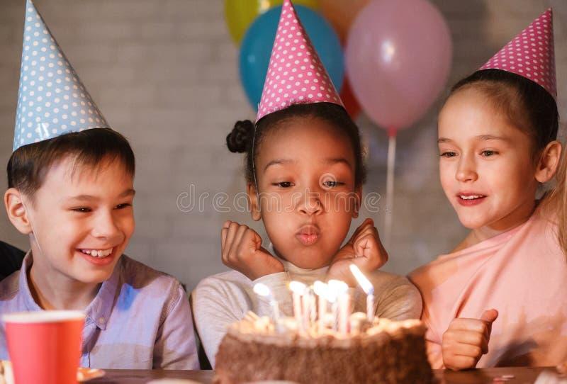 Velas de sopro da menina no bolo de aniversário, comemorando o aniversário foto de stock