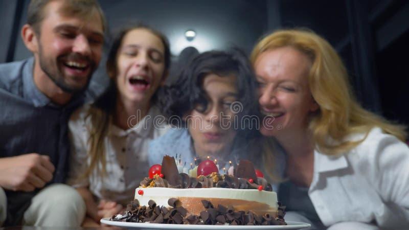 Velas de sopro de sorriso felizes do menino em seu bolo de aniversário crianças cercadas por sua família Bolo de aniversário com  fotos de stock