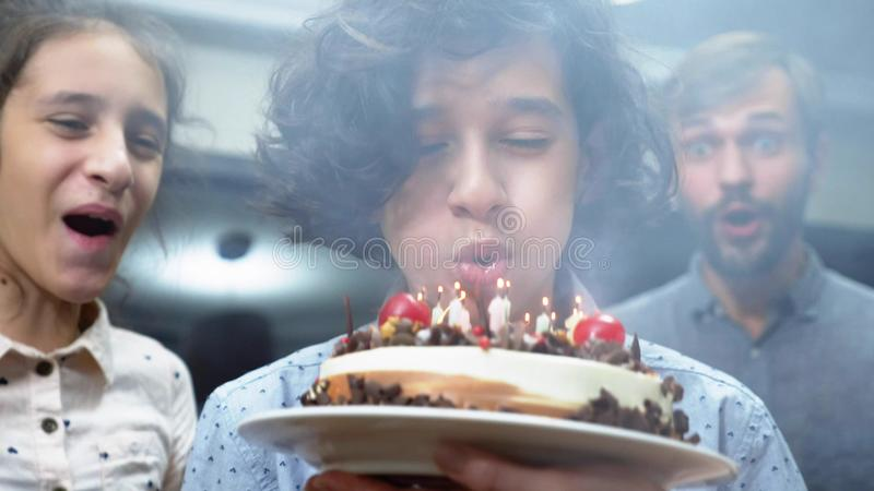 Velas de sopro de sorriso felizes do menino em seu bolo de aniversário crianças cercadas por sua família Bolo de aniversário com  foto de stock royalty free