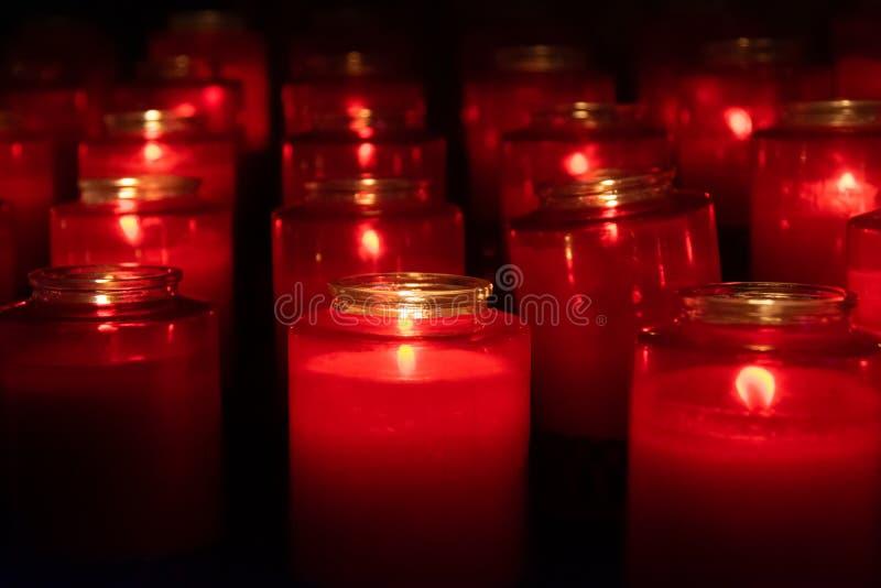 Velas de vidro vermelhas iluminadas em uma igreja escura fotos de stock