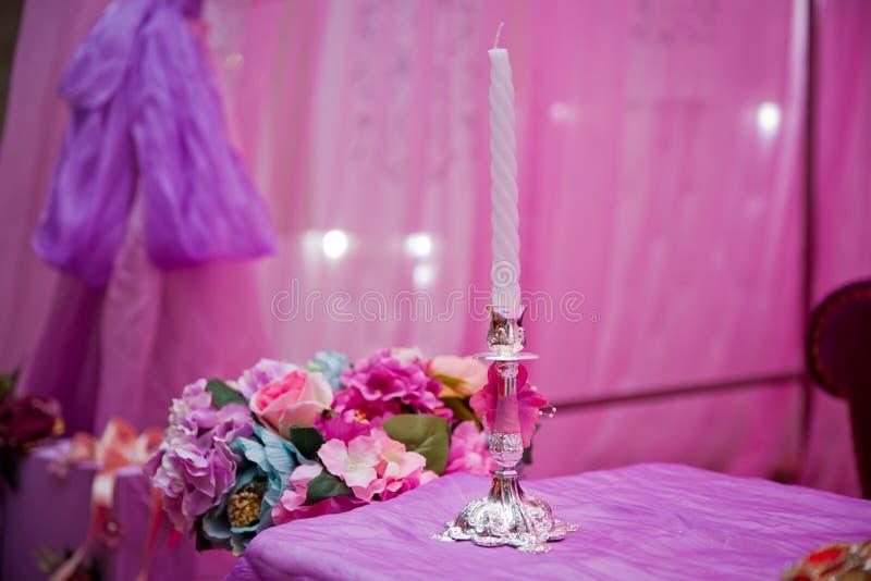 Velas decorativas blancas de fondos rosados Vela hermosa en fondo rosado Vela en el burning de la palmatoria Candelabros retros foto de archivo libre de regalías