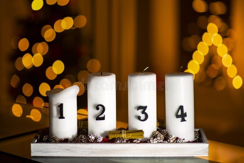 Velas del advenimiento en fila con la decoración en un soporte con el árbol de navidad y una vela del triángulo en un fondo fotografía de archivo