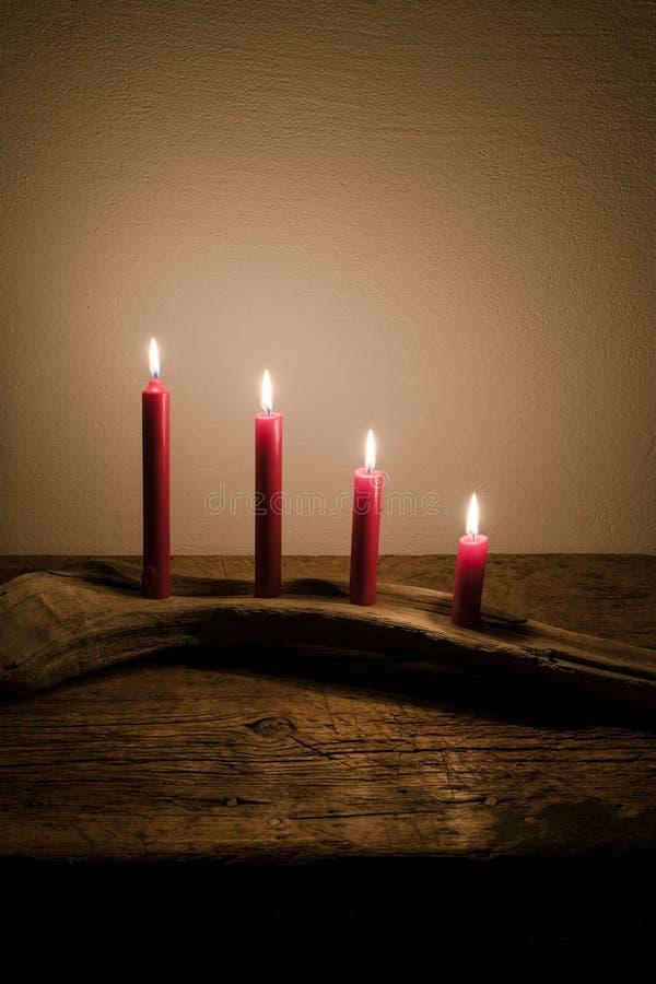 Velas del calendario del advenimiento que queman brillantes en una obra de arte natural hecha de la madera de deriva fotos de archivo