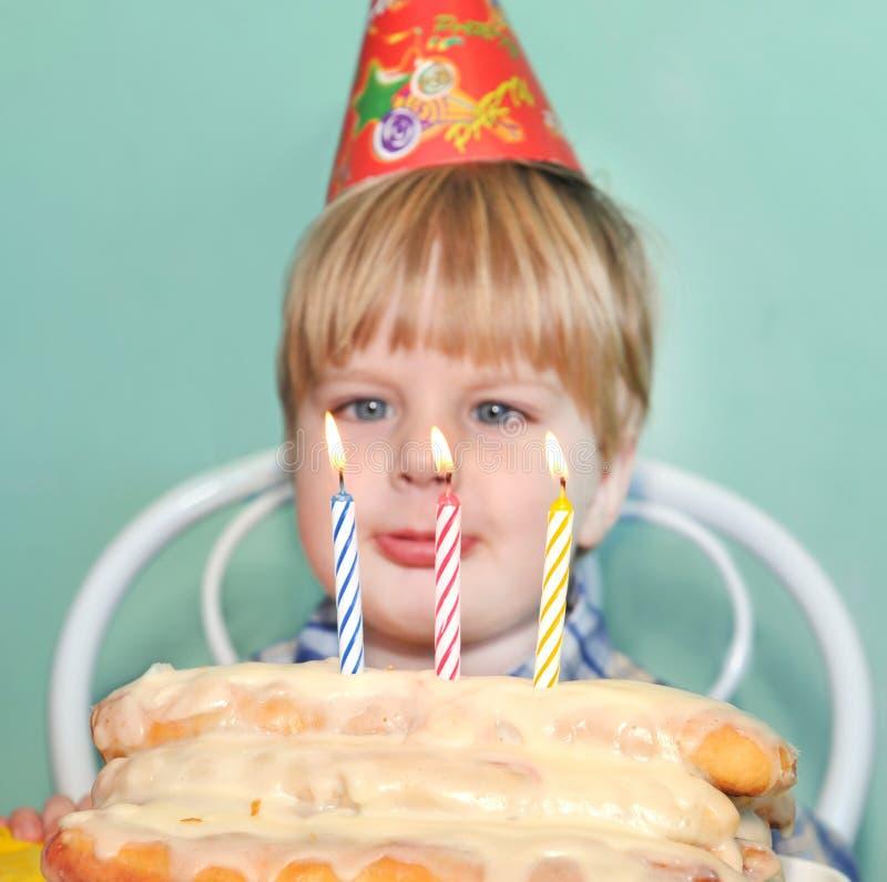 Velas del cumpleaños del muchacho que soplan joven imagenes de archivo