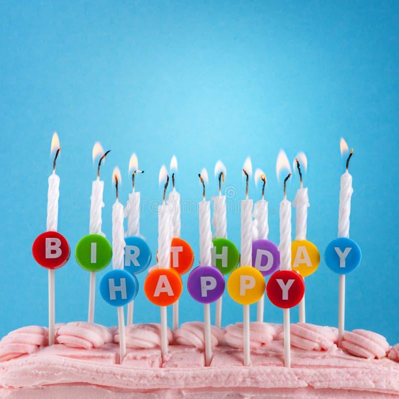 Velas del feliz cumpleaños en fondo azul imagen de archivo