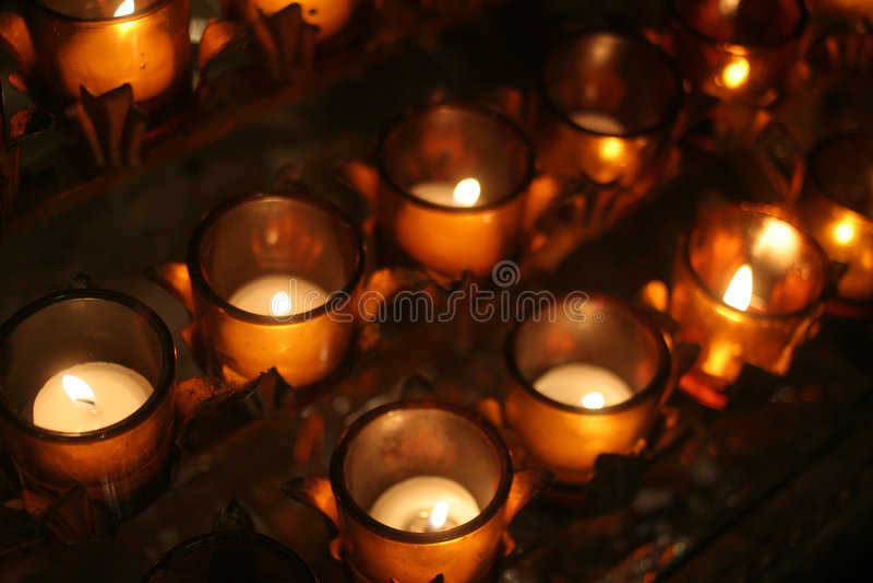 Velas del rezo en una catedral imágenes de archivo libres de regalías