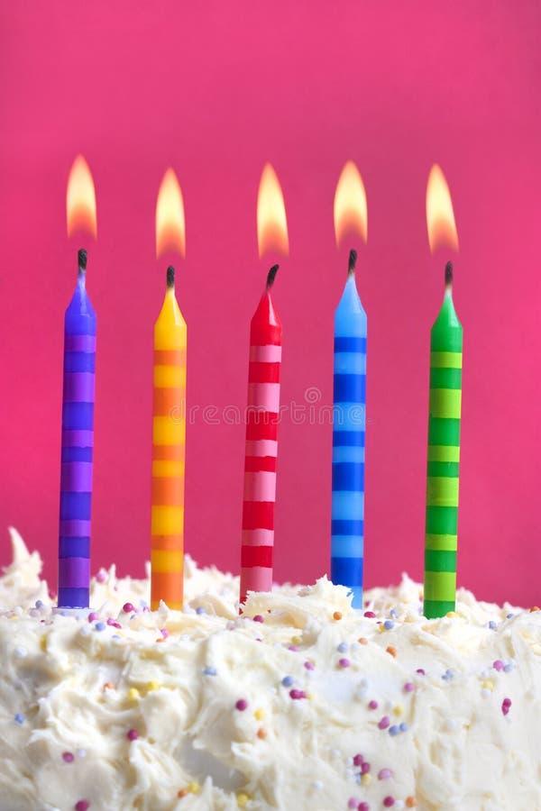 Velas do aniversário em um bolo imagem de stock