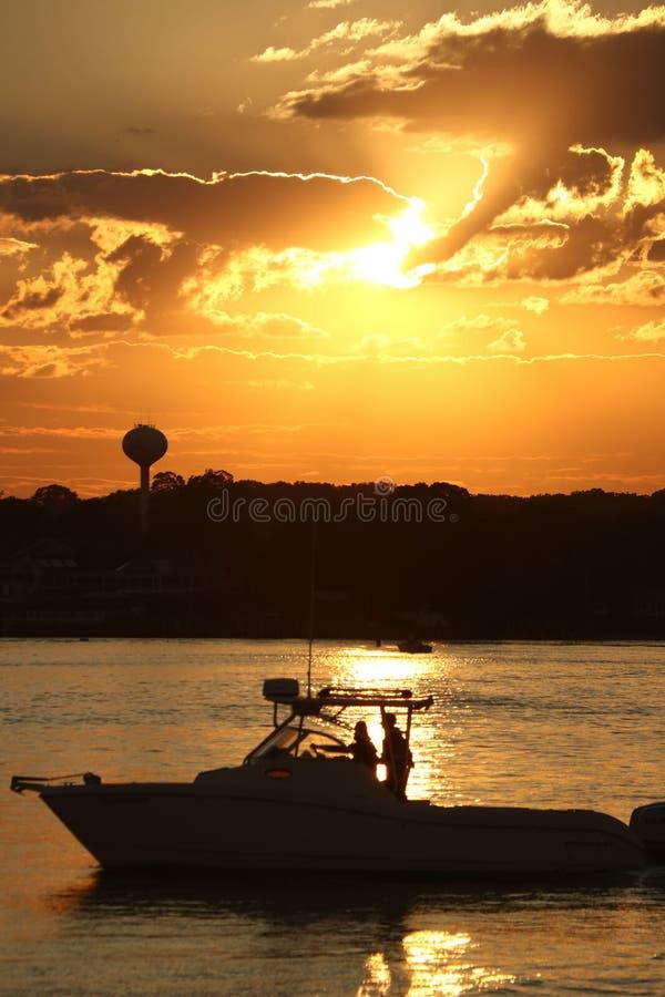Velas do barco através do porto durante o pôr do sol imagens de stock